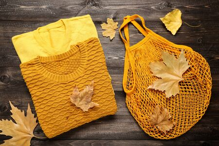 Folded sweaters with autumn leafs and bag on brown wooden table