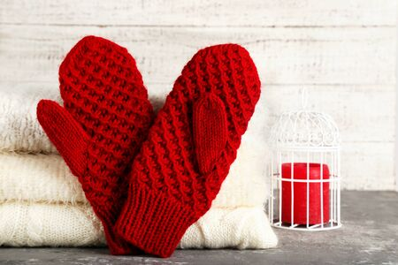 Folded knitted sweaters with pair of gloves and candle on grey table