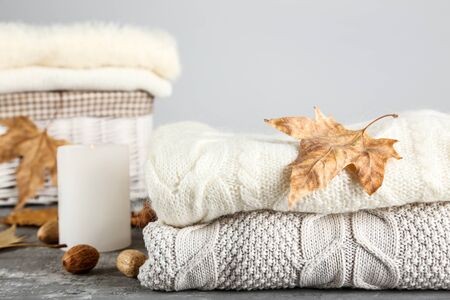 Folded sweaters with autumn leafs and candle on grey background Stock Photo