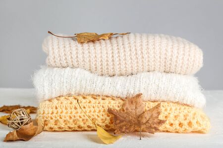 Folded sweaters with autumn leafs on grey background