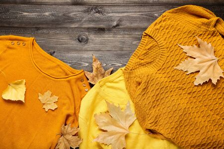 Woolen sweaters with autumn leafs on brown wooden table Stock Photo