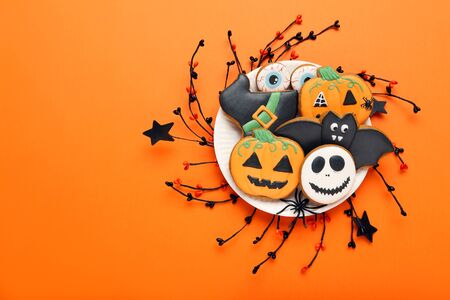 Halloween gingerbread cookies in plate on orange background Imagens