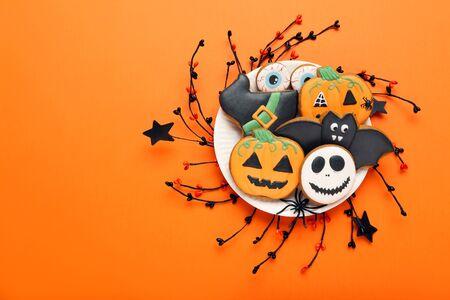Halloween Lebkuchenplätzchen im Teller auf orangem Hintergrund