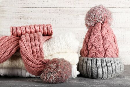 Knitted sweaters with scarf and hat on grey table