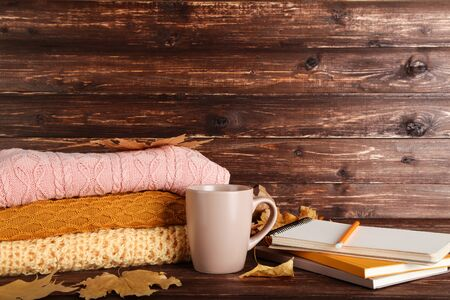 Folded sweaters with autumn leafs, cup of tea and notepads on brown wooden table Stock Photo