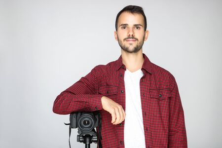 Young photographer with camera on tripod on grey background
