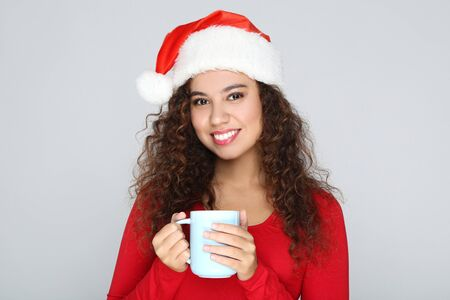 Beautiful american woman wearing santa hat and holding cup of tea on grey background