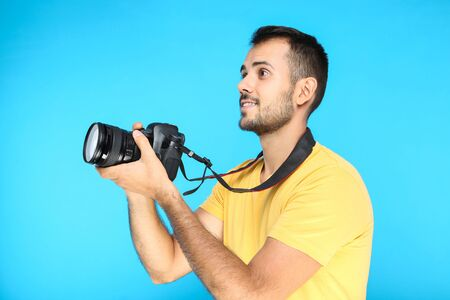 Young photographer with camera on blue background