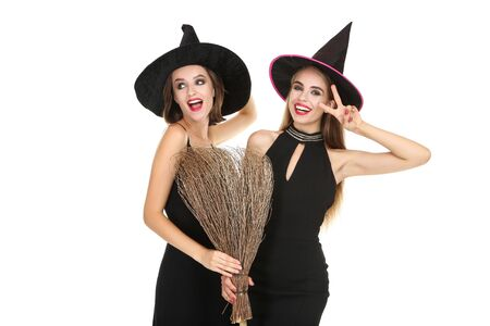 Two young women in black halloween costumes with broom on white background 写真素材