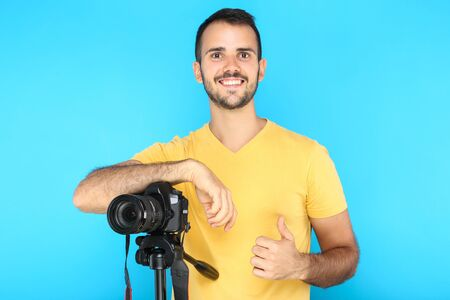 Young photographer showing thumb up with camera on tripod on blue background