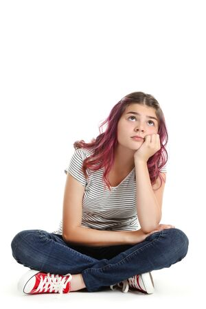 Hermosa joven sentada sobre fondo blanco.