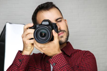 Young photographer with camera and studio equipment on grey background