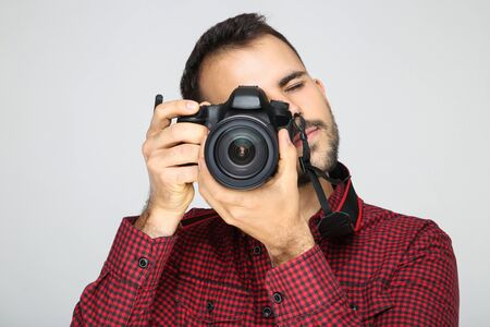 Young photographer with camera on grey background