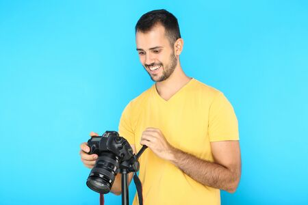 Young photographer with camera on tripod on blue background