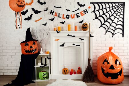 Halloween decorations on white fireplace with orange pumpkins 写真素材
