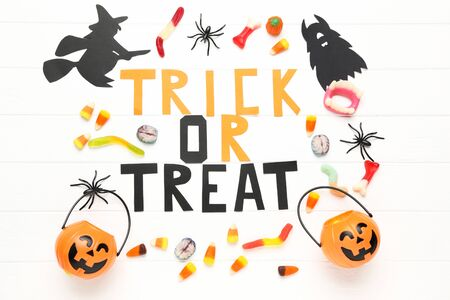 Text Trick or Treat with paper halloween decorations and candies on white background