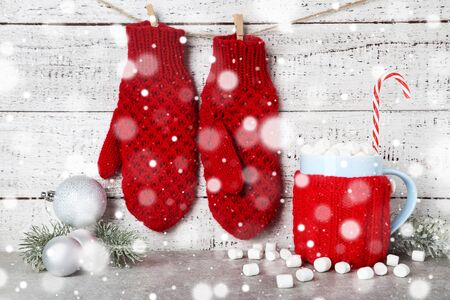 Mitones tejidos con adorno de navidad y taza de bebida caliente sobre fondo blanco de madera
