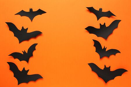 Paper halloween bats on orange background