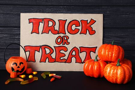 Text Trick or Treat with halloween pumpkins and candies on wooden background Stok Fotoğraf