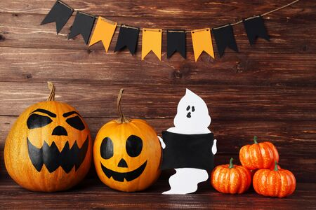 Halloween pumpkins with paper ghost and flags on brown wooden background