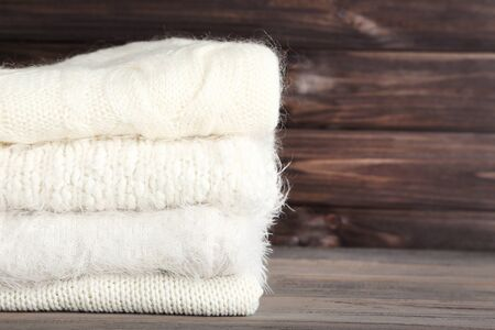 Folded knitted sweaters on wooden background Imagens