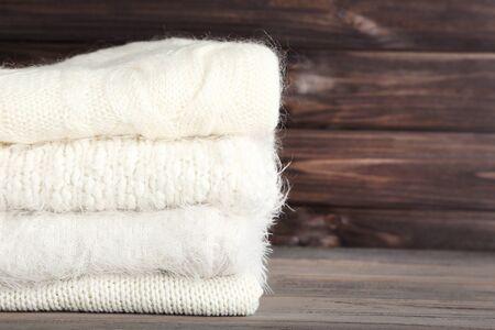 Suéteres de punto doblado sobre fondo de madera Foto de archivo