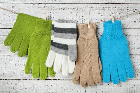 Knitted mittens hanging on white wooden background