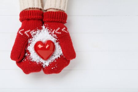 Hands in knitted mittens holding red heart on white wooden table
