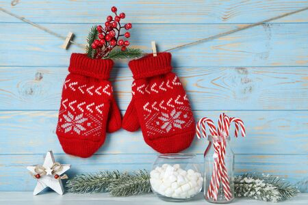 Knitted mittens with fir tree branches, candies, marshamllow and red berries on blue wooden background