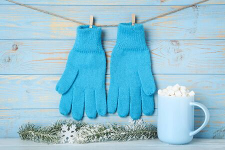 Knitted mittens with fir tree branches and cup of drink on blue wooden background