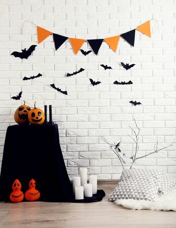 Halloween decorations with pumpkins, paper bats, flags and soft pillows