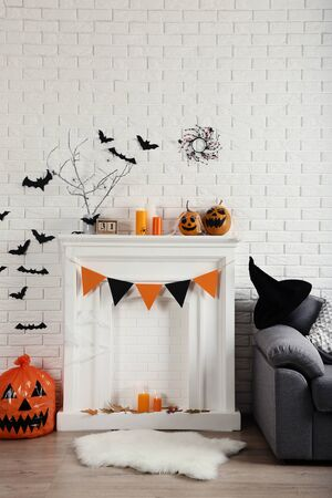 Halloween decorations on white fireplace with orange pumpkins and grey couch Stok Fotoğraf