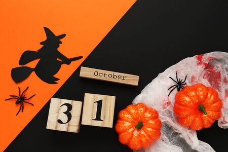 Halloween pumpkins with wooden calendar, spider and paper witch