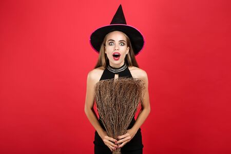 Beautiful woman in halloween costume holding broom on red Stock Photo