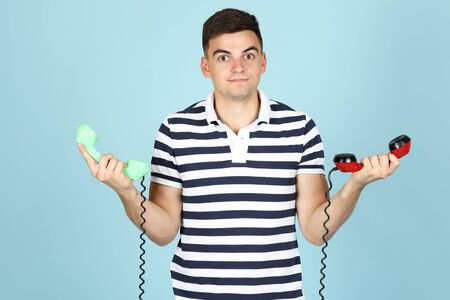 Young man with handsets on blue background