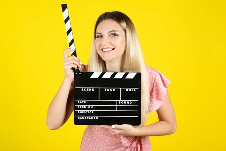 Young woman with blank clapper board on yellow background