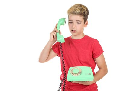 Young boy with handset and telephone on white background