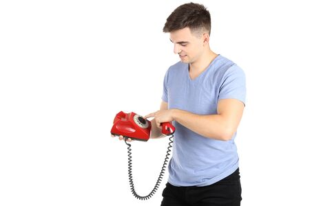 Young man with handset and telephone on white background