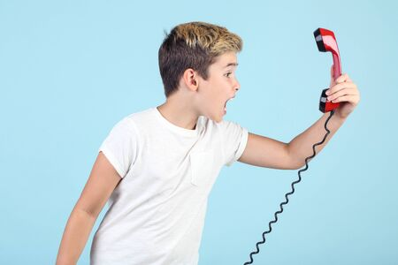 Young boy screaming in handset on blue background
