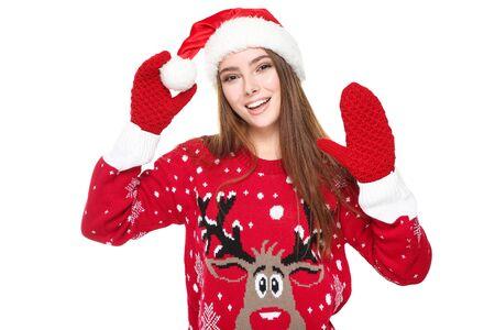 Hermosa mujer vestida con suéter de Navidad, guantes y gorro de Papá Noel sobre fondo blanco. Foto de archivo