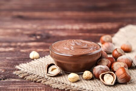 Melted chocolate with hazelnuts on brown wooden table Standard-Bild - 133206866