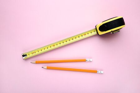 Construction roulette with pencils on pink background