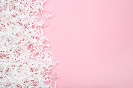White shredded paper on pink background