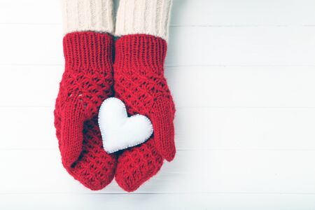 Hands in knitted mittens holding heart on white wooden table