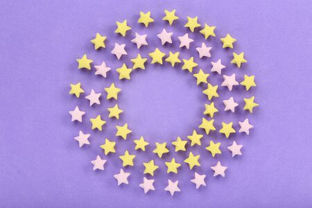 Colorful paper stars on purple background