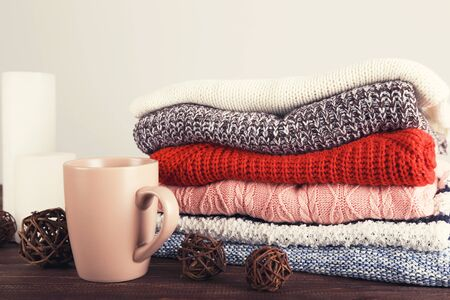 Folded knitted sweaters with cup of tea on grey background