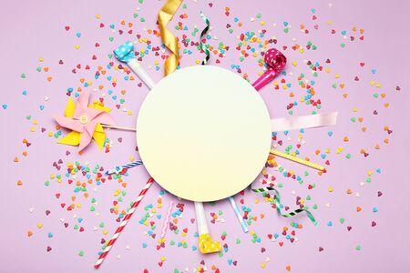 Kleurrijke platliggende compositie met verschillende feestartikelen op paarse achtergrond