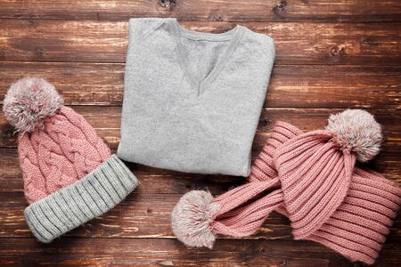 Knitted sweater with hat and scarf on brown wooden table