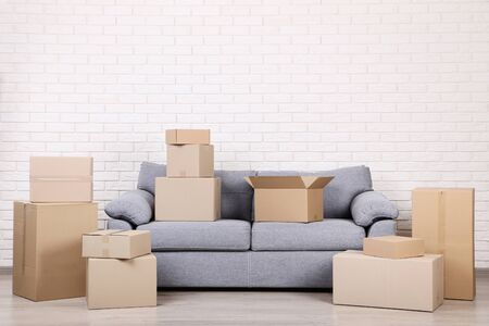 Cardboard boxes with grey sofa on brick wall background