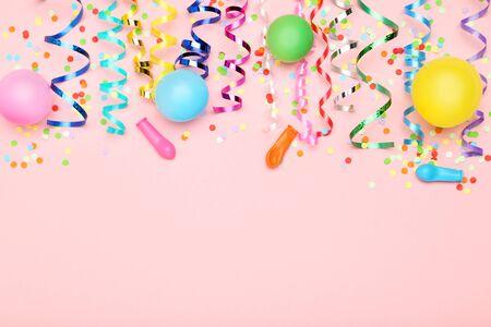 Cintas de colores con globos de goma y confeti sobre fondo rosa